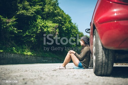 Young caucasian cute woman sitting by a broken down car.