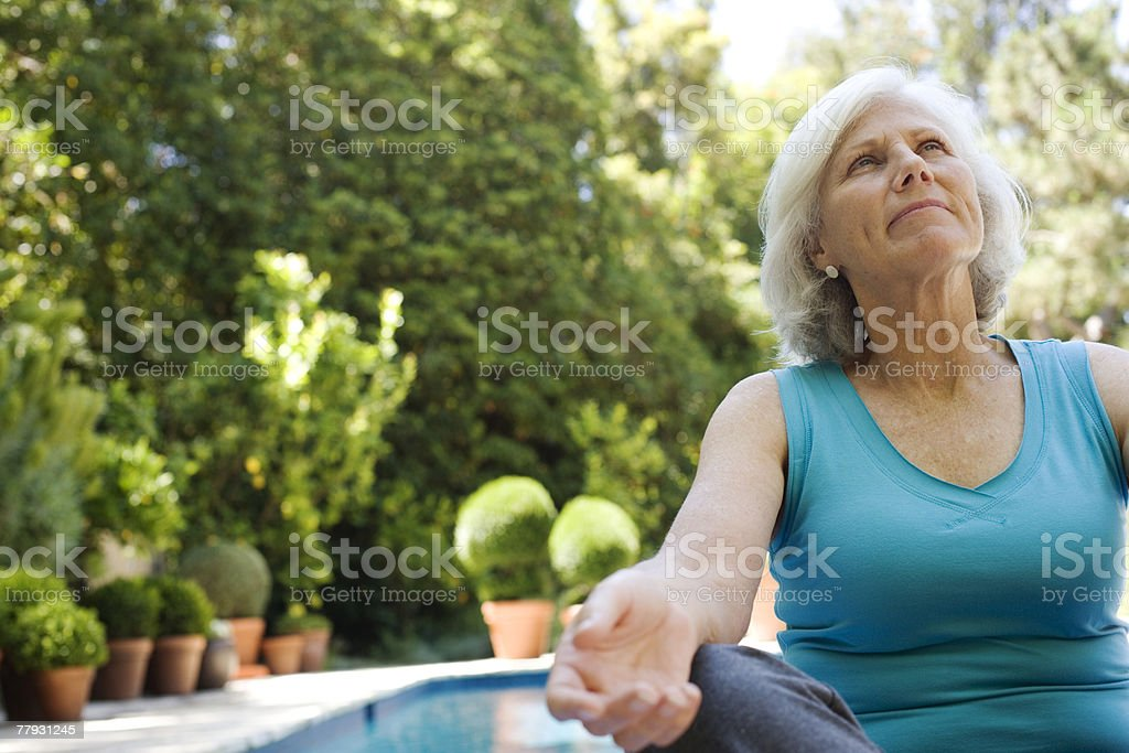 Woman sitting by outdoor pool looking up stock photo