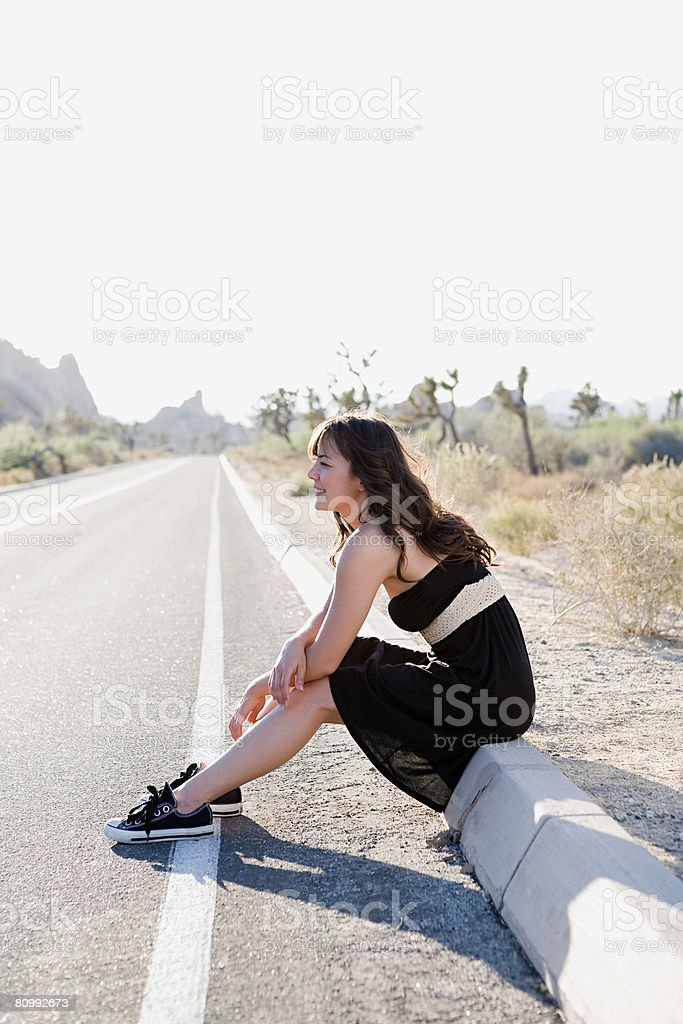 Woman sitting by road stock photo