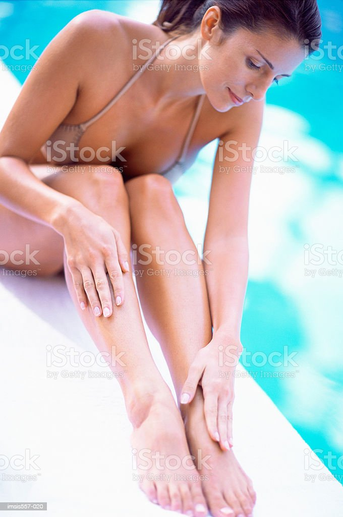 Woman sitting by swimming pool royalty-free stock photo