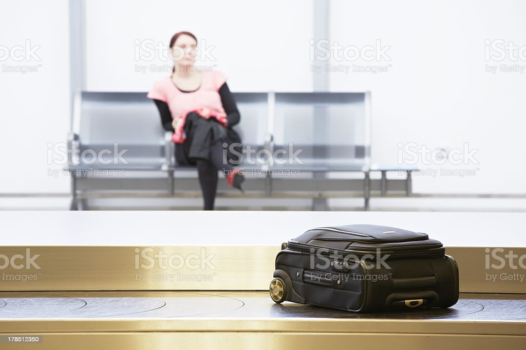 Woman sitting by the baggage claim belt in an airport stock photo
