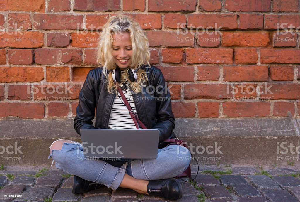 woman sitting by the brick wall and working on laptop