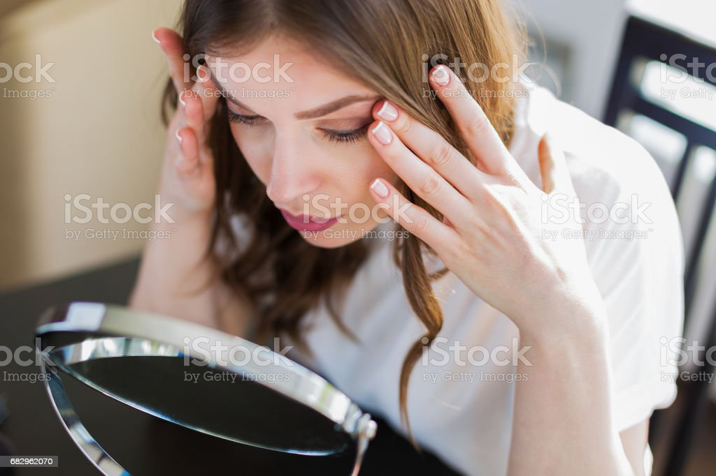 Woman sitting by the mirror stock photo
