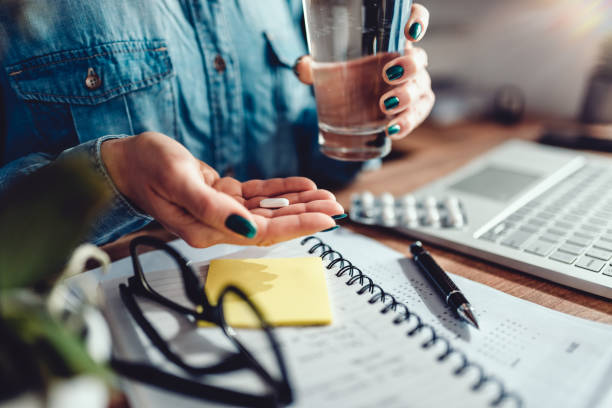 Woman sitting by the office desk and taking medical pills Woman wearing denim shirt sitting by the desk in the office and taking medical pills woman taking pills stock pictures, royalty-free photos & images