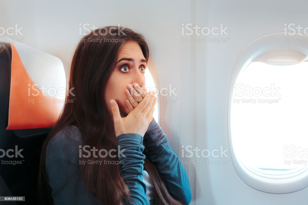 Woman Sitting By the Window on An Airplane Feeling Sick stock photo