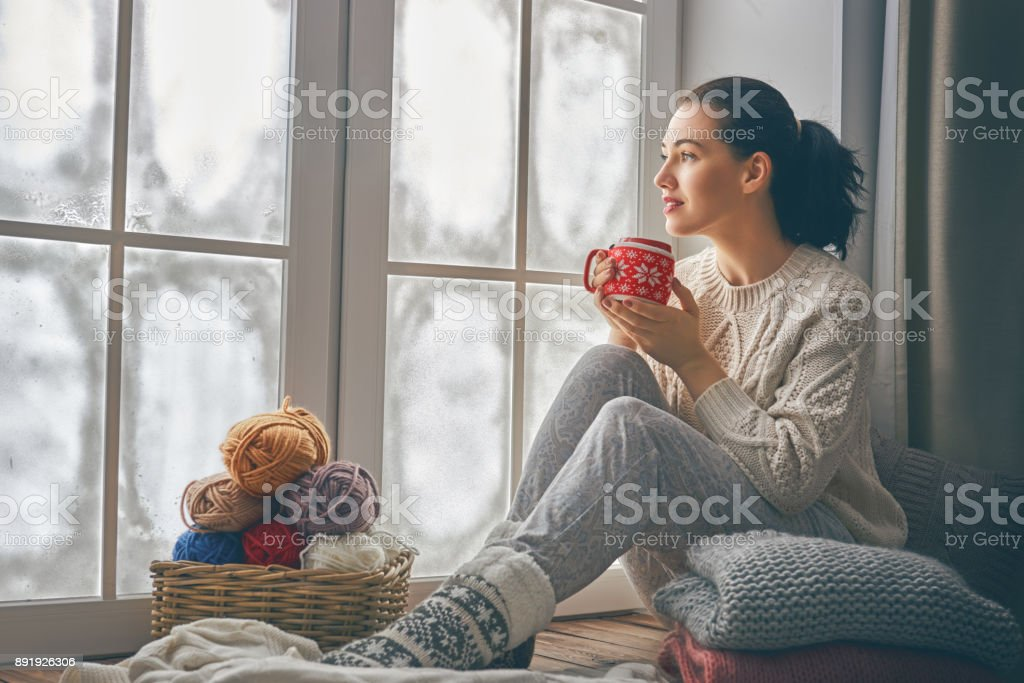 woman sitting by the window stock photo
