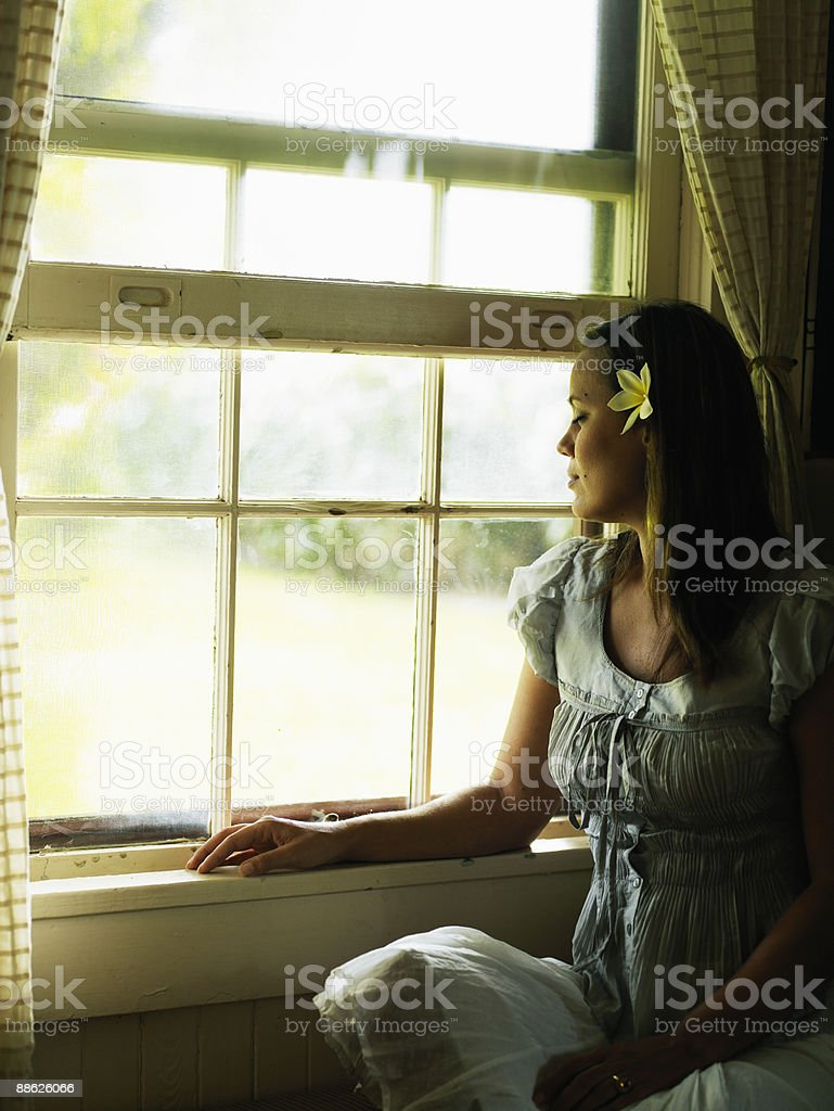 Woman sitting by window facing out eyes closed royalty-free stock photo