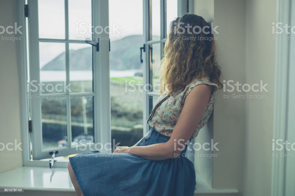 Woman sitting by window of rural home stock photo