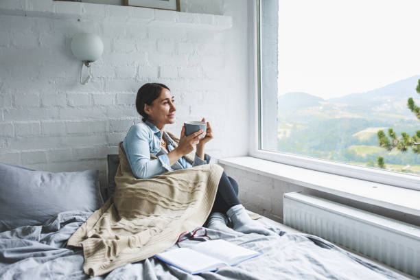 Woman sitting comfortable and looking through the window stock photo
