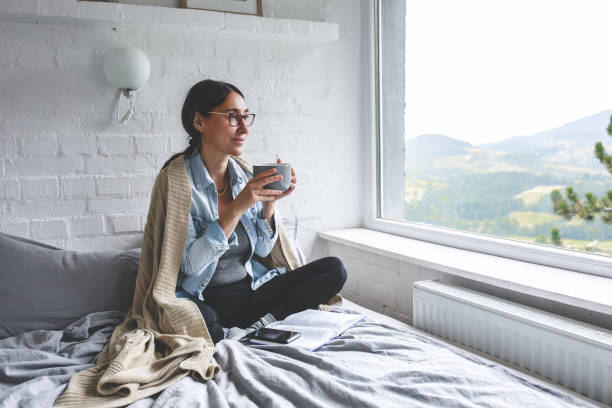 Woman sitting comfortable drinking tea and looking through window stock photo