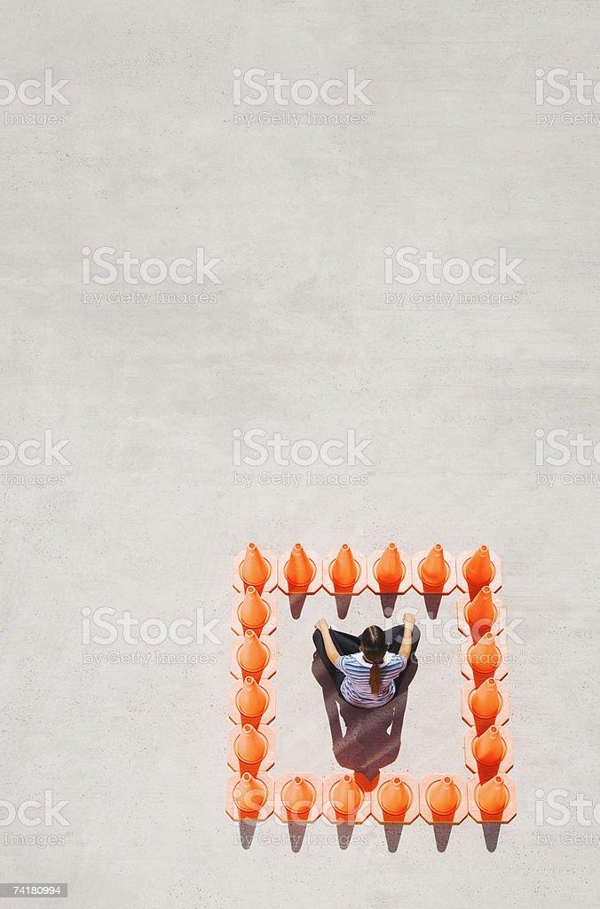 Woman sitting cross legged inside box of traffic cones royalty-free stock photo