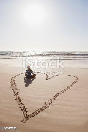istock Woman sitting cross-legged in heart on beach 116377232