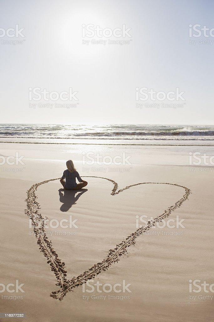 Femme assise Assis en tailleur de cœur sur la plage - Photo
