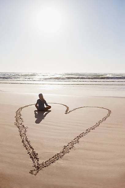 woman sitting cross-legged in heart on beach - conceptual symbol stock pictures, royalty-free photos & images