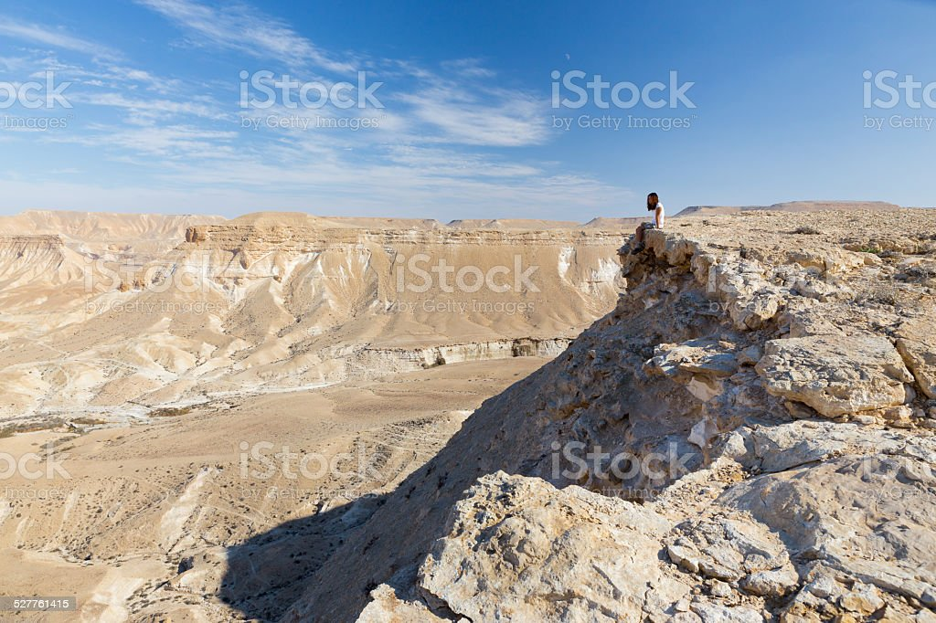 Woman sitting desert mountain edge. stock photo