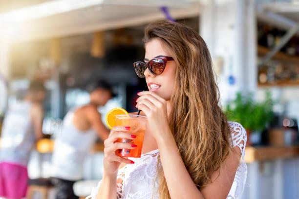 Woman sitting in a beach bar and enjoying a aperitif - foto stock