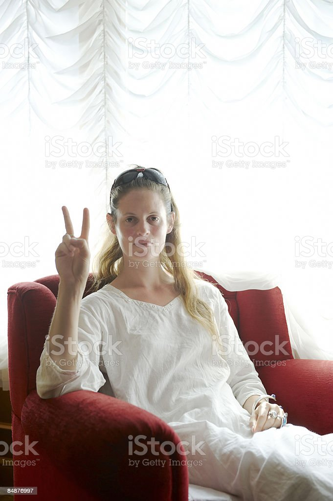 woman sitting in a chair making a peace sign royalty-free stock photo