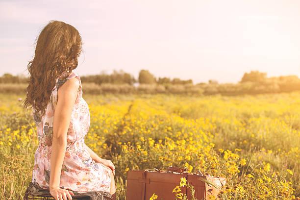 Frau sitzt im einem Feld Blick weit entfernt – Foto