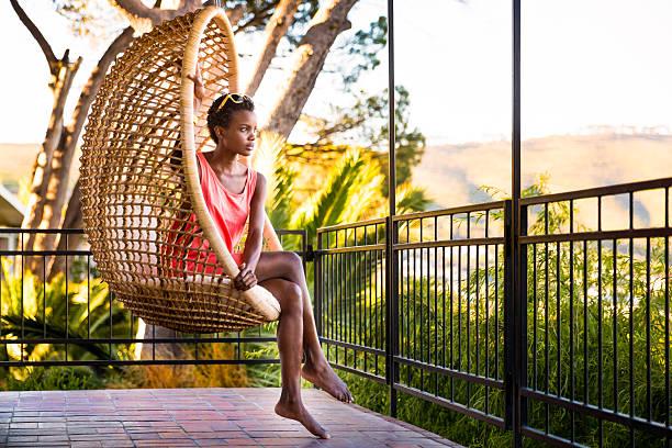 woman sitting in a hanging chair - schommelen bungelen stockfoto's en -beelden