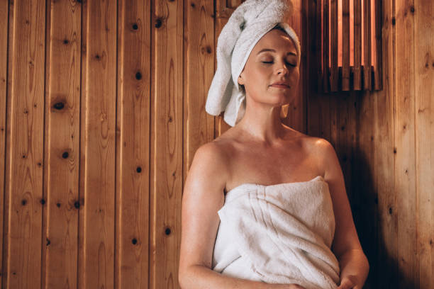 Woman sitting in a spa with eyes closed Woman with towel wrapped around her body and head sitting in sauna spa peacefully. Woman relaxing in a wooden spa with eyes closed. sauna stock pictures, royalty-free photos & images