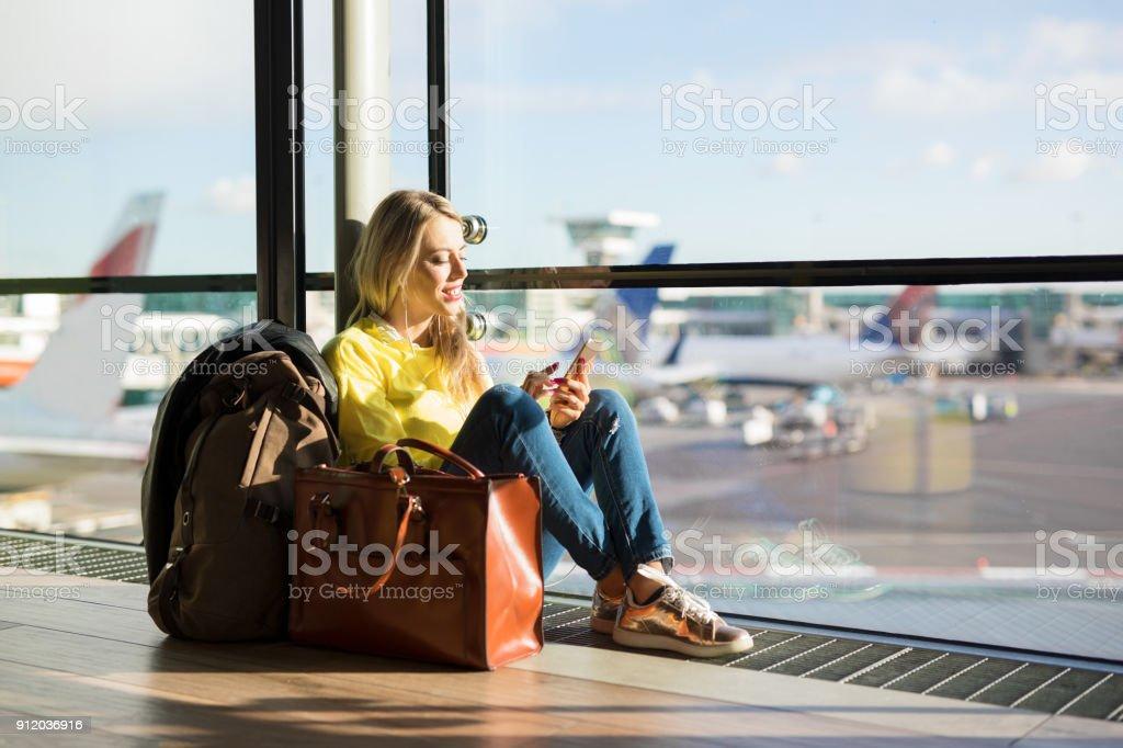 Mujer sentada en el aeropuerto y a la espera de su vuelo foto de stock libre de derechos