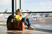 istock Woman sitting in airport and waiting for her flight 912036916
