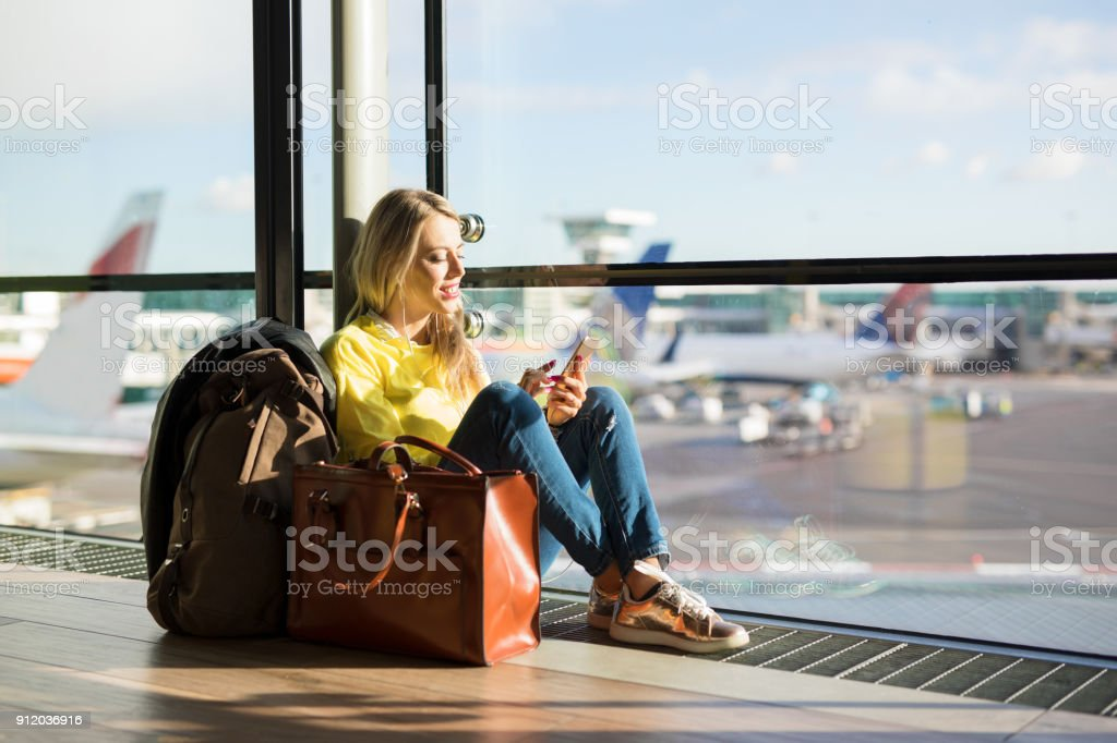 Woman sitting in airport and waiting for her flight stock photo