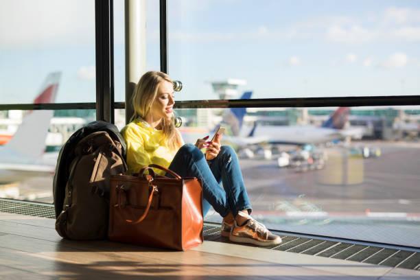 frau sitzt am flughafen und warten auf ihren flug - handytasche stock-fotos und bilder