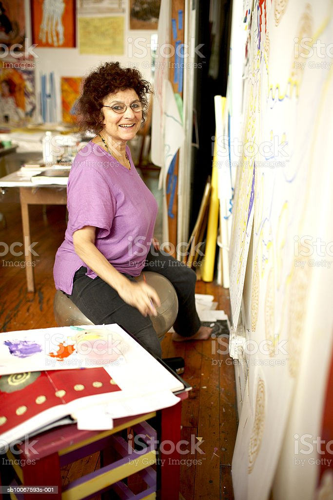 Woman sitting in art studio, smiling, portrait royalty free stockfoto