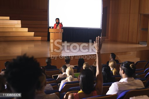 1133856033 istock photo Woman sitting in audience raising hand for asking question 1133855326