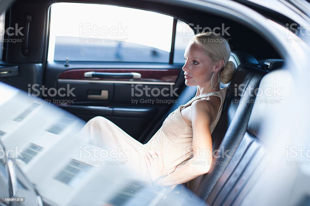Woman sitting in backseat of limo stock photo