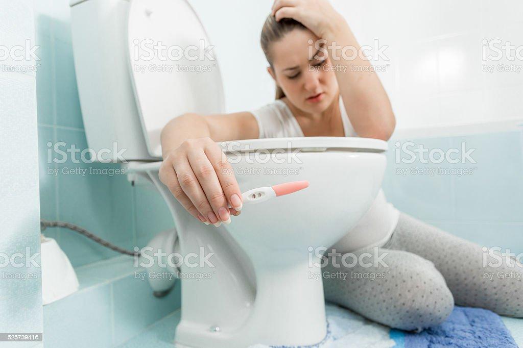 Vasca Da Bagno Gravidanza : Donna seduta in bagno e con test di gravidanza positivo fotografie