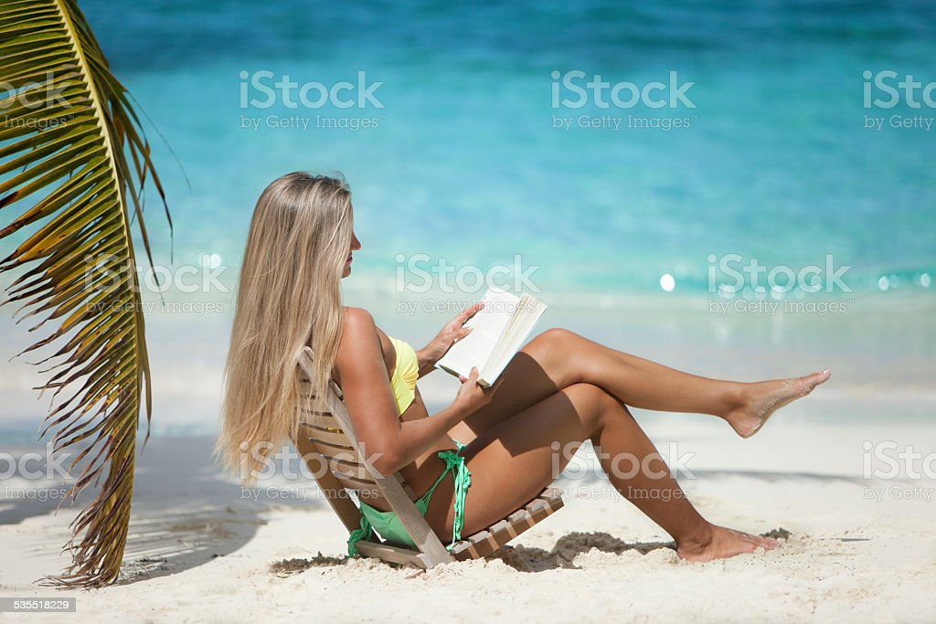 Woman Sitting In Beach Chair And Reading A Book Stock Photo Download Image Now Istock