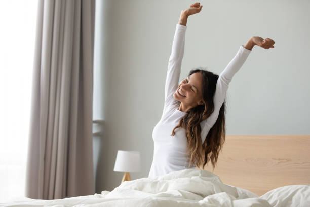 Woman sitting in bed stretching her arms muscles after sleep Happy woman in white nightwear sitting in bed awakened from enough and healthy sleep feels good, stretching her arms muscles after sleep and long immobility wakes up start new day with smile concept fresh start morning stock pictures, royalty-free photos & images