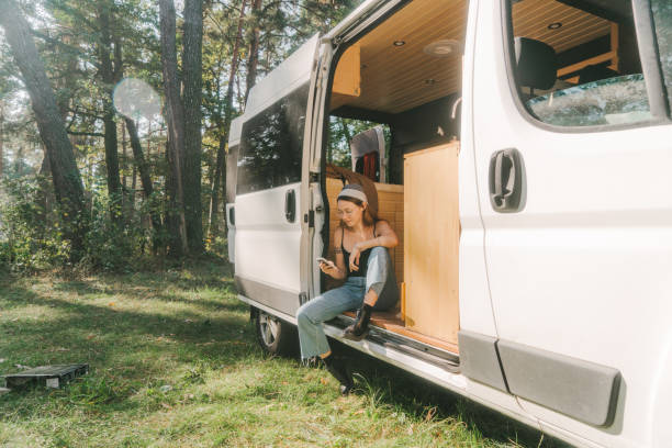 Woman sitting in camper van and using smartphone Woman sitting in camper van in forest  and using smartphone rv interior stock pictures, royalty-free photos & images