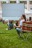 istock woman sitting in camping chair watching movie at open air cinema 1267095032