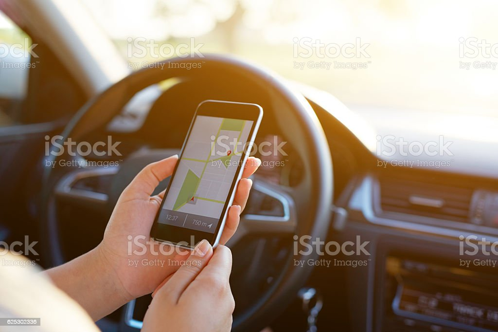 Woman sitting in car and holding mobile phone stock photo