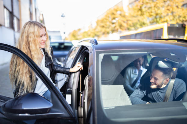 Woman Sitting In Car With Friends stock photo