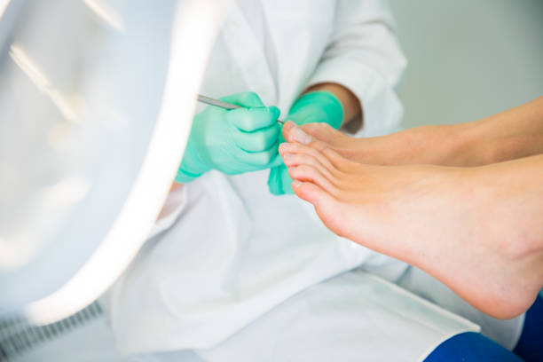 Woman sitting in chair, having foot treatment in spa salon. Woman sitting in chair, having foot treatment in spa salon.  Professional medical pedicure specialist in protective mask using special electric lathe and tools. podiatry stock pictures, royalty-free photos & images