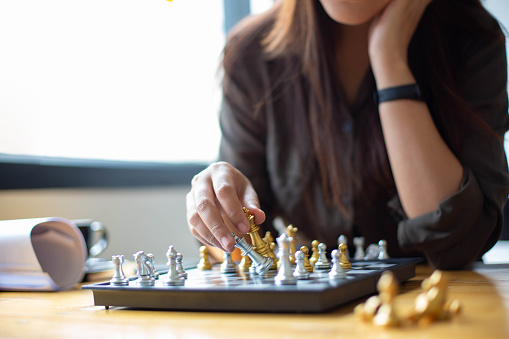 A woman sitting in chess May be interpreted in the planning of the competition in the business.