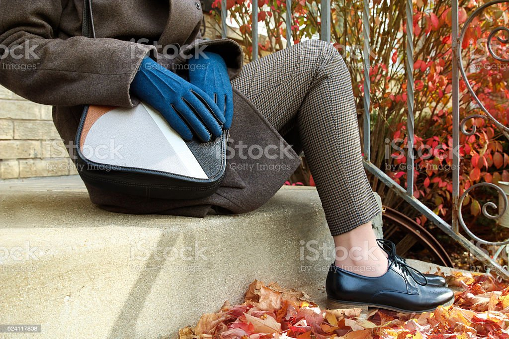 woman sitting in coat with bag and  black classic shoes stock photo