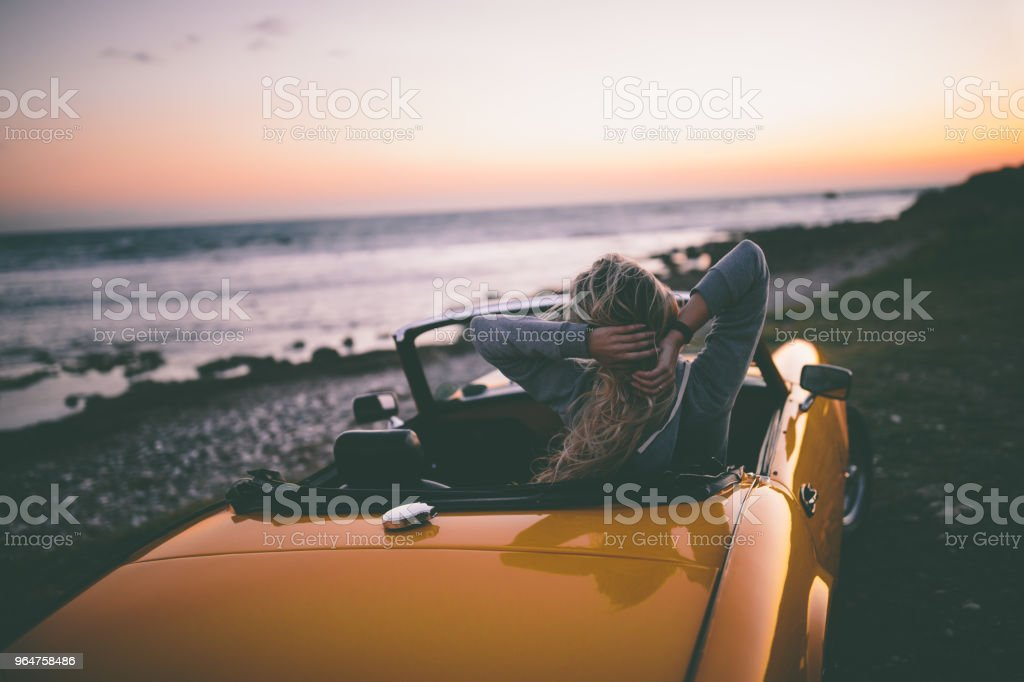 Woman sitting in convertible car and looking at the sea royalty-free stock photo