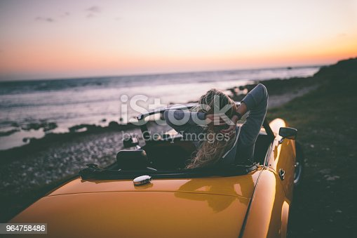 147878016 istock photo Woman sitting in convertible car and looking at the sea 964758486