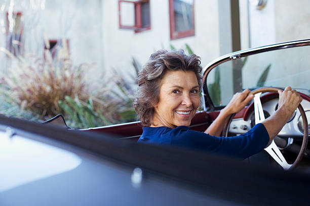 Frau sitzt in Cabrio Auto lächelnd über der Schulter – Foto