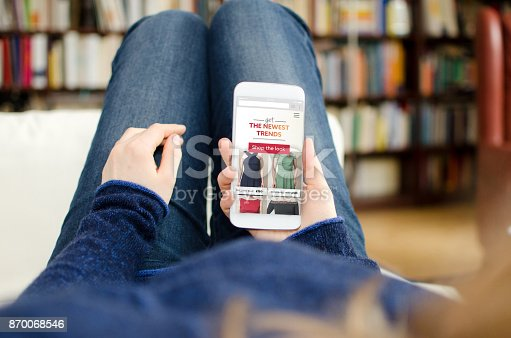 The woman is shopping online in a webshop. The photo was taken out of a personal perspective by looking over her shoulder.
