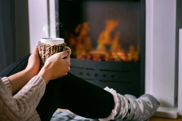woman sitting in front of the fireplace and holding cup of tea in hand on legs - warm house stock photos and pictures