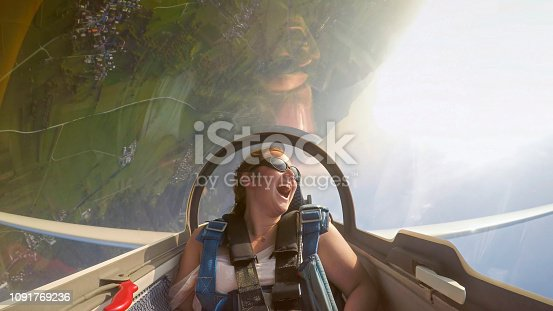 Smiling young woman looking at view while sitting in glider airplane.