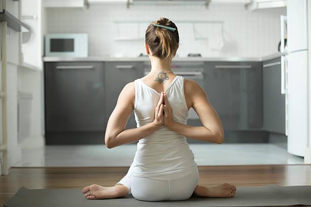 woman sitting in gomukasana pose - gymnastik tattoo stock-fotos und bilder