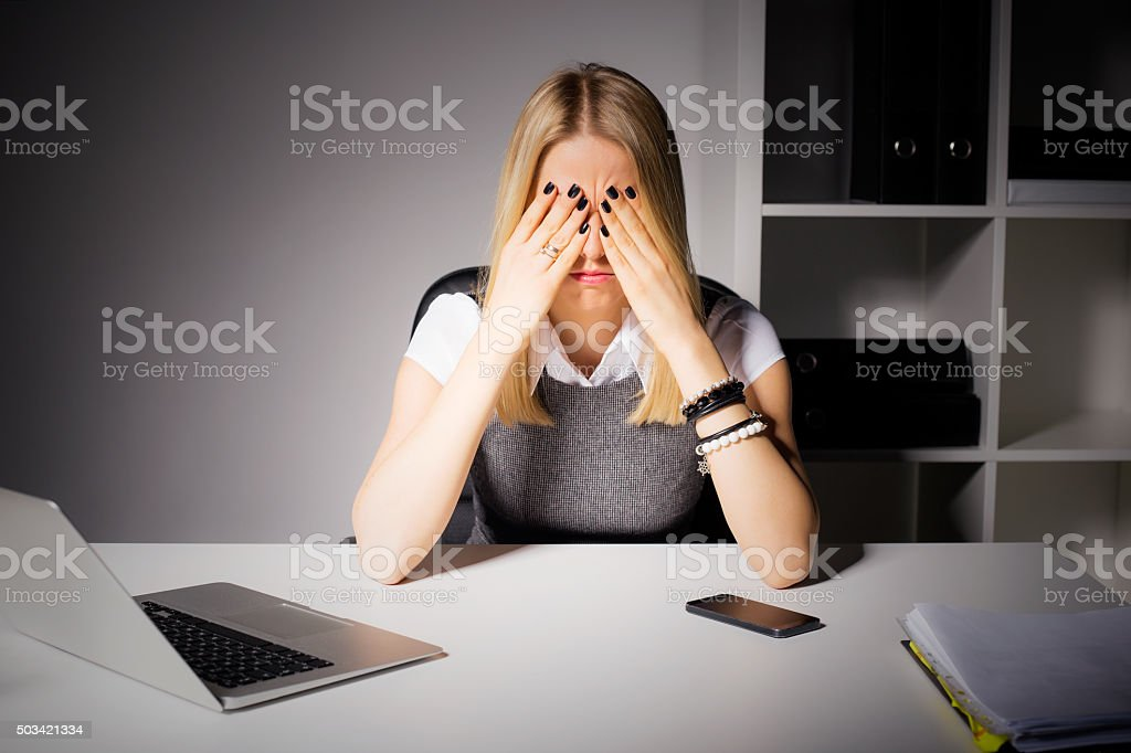 Woman sitting in her office with her eyes covered stock photo