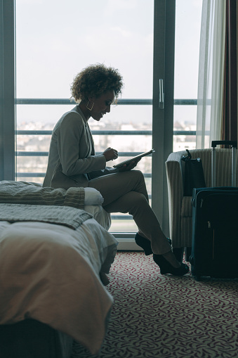 Woman Sitting In Hotel Room And Using Digital Tablet Stock Photo - Download Image Now